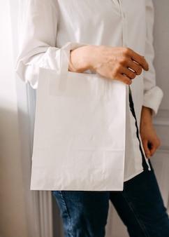 Zbliżenie kobiety trzymającej białą pustą papierową torbę