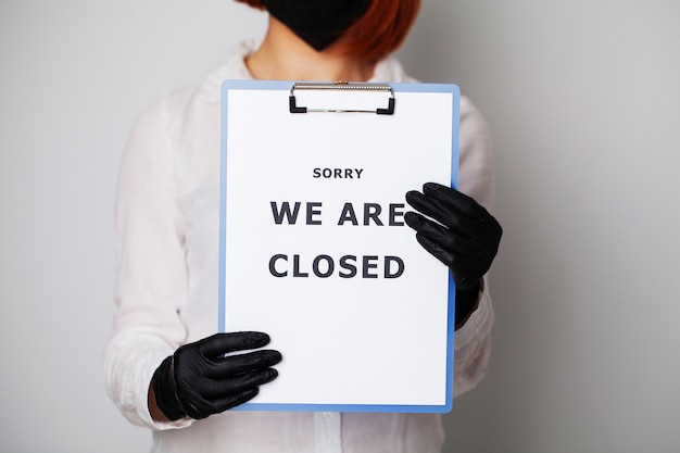 Zbliżenie kobiety trzymającej puste z napisem jesteśmy zamknięci wzywając do zaprzestania rozprzestrzeniania covid-19.