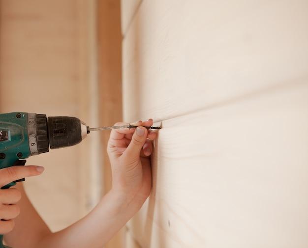 Zbliżenie kobiety trzymającej śrubę i śrubokręt elektryczny