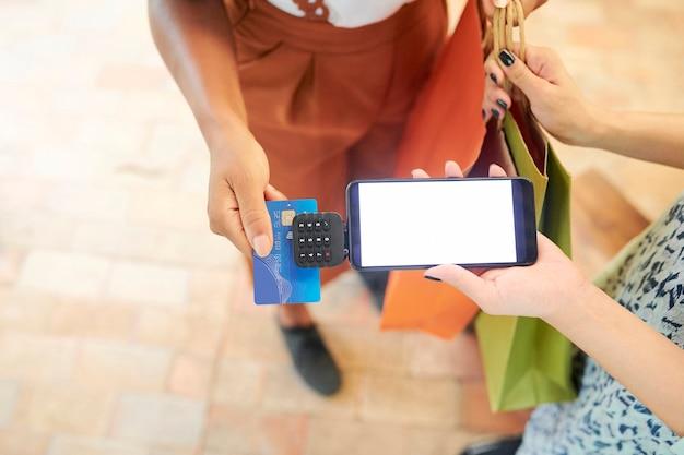 Zbliżenie kobiety trzymającej torby na zakupy i płacącej za zakup kartą kredytową do sprzedawczyni z terminalem