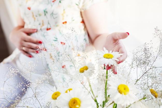Zbliżenie kobiety w ciąży trzymając kwiat i dotykając jej brzucha