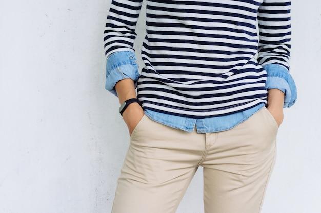 Zbliżenie kobiety w dżinsowej koszuli, pasiastej koszulce i beżowych spodniach z monitorem fitness na dłoni