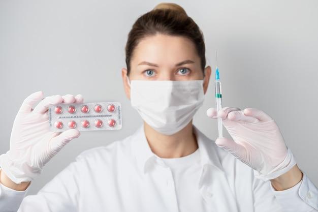 Zbliżenie kobiety w ochronnej masce na twarz z blistrem tabletek i strzykawką