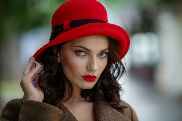 Zbliżenie kobiety w wieku 28-30 lat z ciemnymi włosami w eleganckim płaszczu i czerwonymi dodatkami