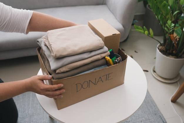 Zbliżenie kobiety wkładającej ubrania do pudełka na darowizny