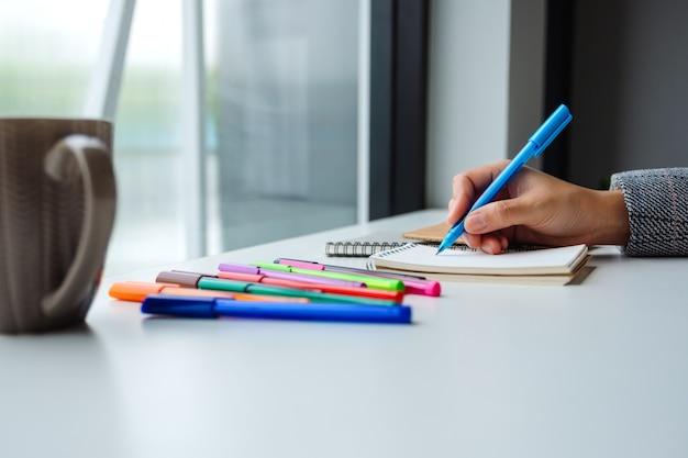 Zbliżenie kobiety writing na pustym notatniku z barwionymi piórami i filiżanką kawy na stole