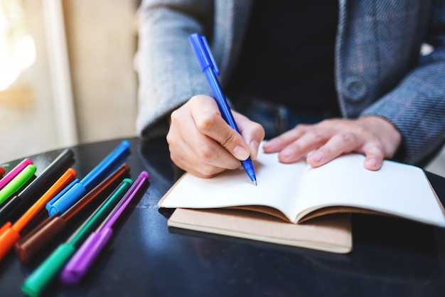 Zbliżenie kobiety writing na pustym notatniku z barwionymi piórami na stole