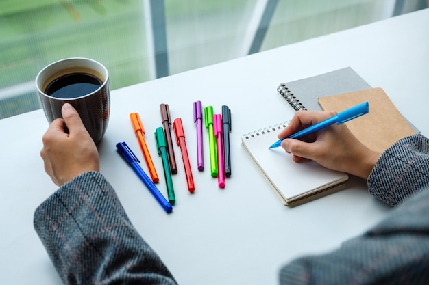 Zbliżenie kobiety writing na pustym notatniku z barwionymi piórami podczas gdy pijący kawę