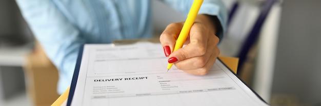 Zbliżenie kobiety wypełniania dokumentu odbioru dostawy.