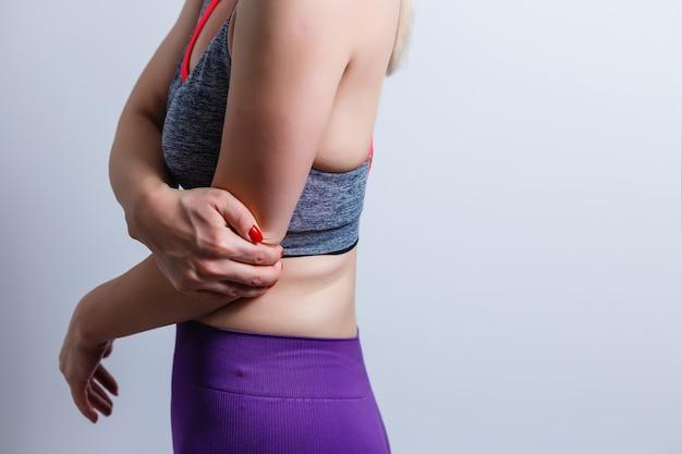 Zbliżenie kobiety z bólem łokcia na białym tle