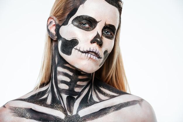 Zbliżenie kobiety z halloweenowym szkieletowym makijażem na białym tle
