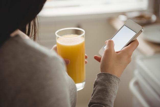 Zbliżenie kobiety za pomocą inteligentnego telefonu, trzymając napój