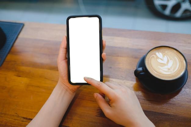 Zbliżenie kobiety za pomocą mobilnego pustego inteligentnego telefonu i karty kredytowej wysyłającej masaże w kawiarni