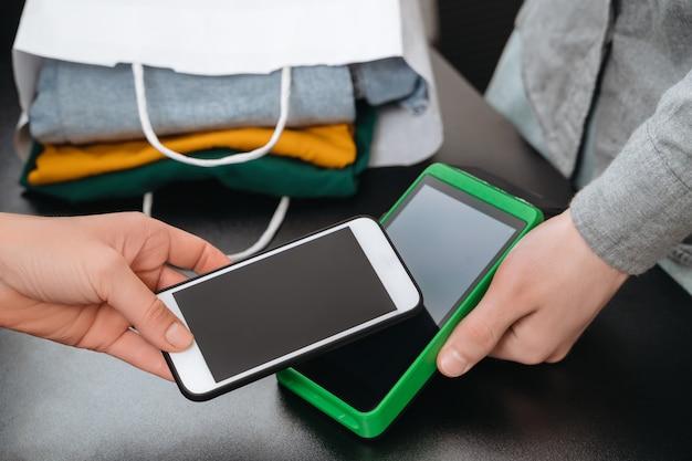 Zbliżenie kobiety za pomocą smartfona do płatności zbliżeniowych za zakup w sklepie odzieżowym