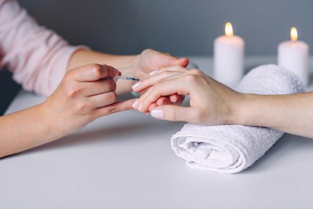 Zbliżenie kobiety zdrowe naturalne paznokcie w salonie piękności. manikiurzystka maluje paznokcie klienta.