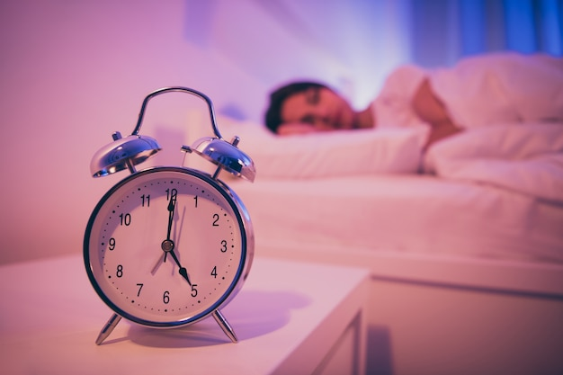 Zbliżenie kobiety zegar sygnału dzwonka leżącego w łóżku
