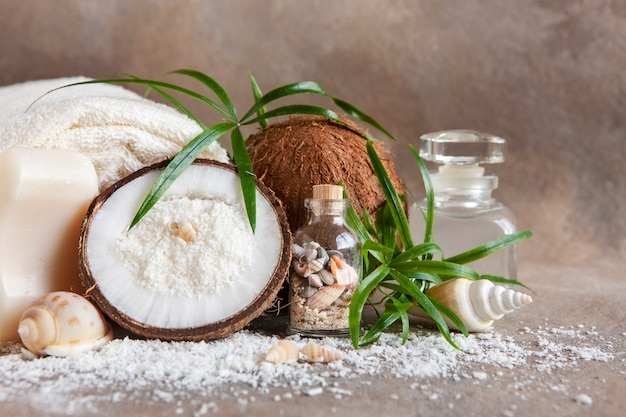 Zbliżenie: kokos, miękkie ręczniki, esencja kokosowa, muszle i tropikalne warzywa.