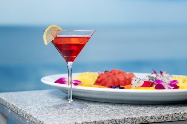 Zbliżenie: koktajl jest kosmopolityczny z plasterkiem cytryny, a obok niego talerz z egzotycznymi owocami: arbuzy, ananasy, smocze owoce. impreza na plaży. impreza w basenie.