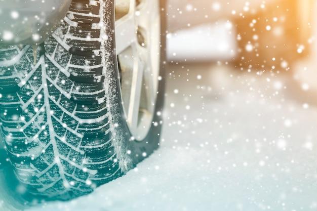 Zbliżenie kół gumowych opon samochodowych w głębokim śniegu zimowym