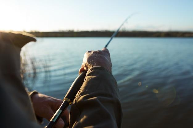 Zbliżenie koło wędki, człowiek łowienie z pięknym zachodem słońca.