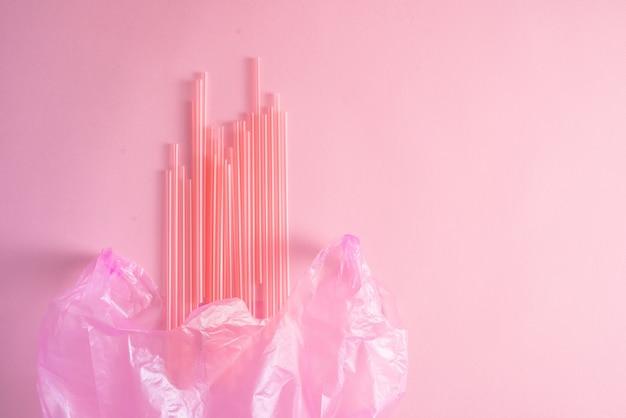 Zbliżenie kolorowe odpady z tworzyw sztucznych w różowym worku na śmieci jako jednorazowego użytku sztućce zanieczyszczenia śmieci koncepcja recyklingu na białym tle na różowym tle