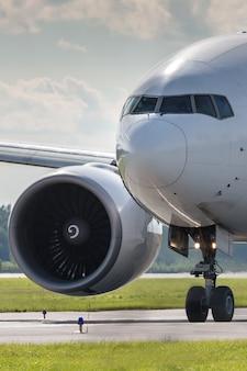 Zbliżenie kołowania samolotu pasażerskiego na pasie startowym w letni dzień