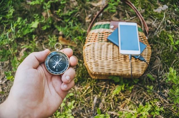 Zbliżenie, kompas w dłoni faceta. w tle powerbank ze smartfonem na koszyku w lesie.