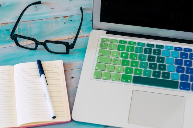 Zbliżenie komputera w okularach i notatniku z piórem na stole z niebieskim tłem