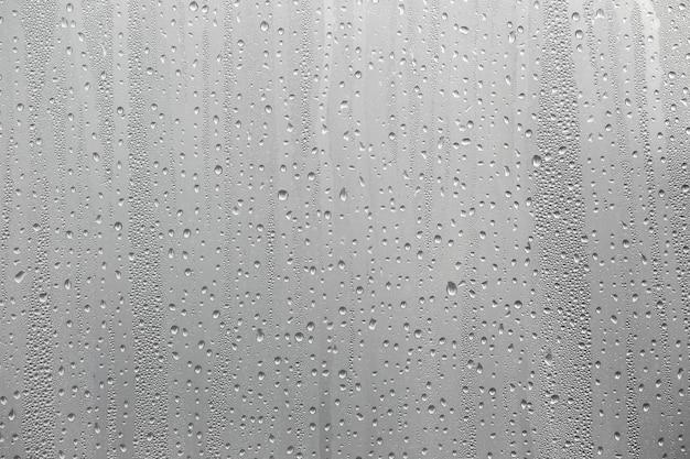 Zbliżenie kondensacji wody na tle szyby okiennej.
