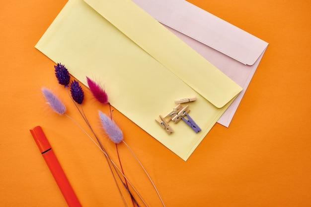Zbliżenie koperty pocztowe i spinacze, pomarańczowe tło. artykuły biurowe, akcesoria szkolne lub edukacyjne, narzędzia do pisania i rysowania