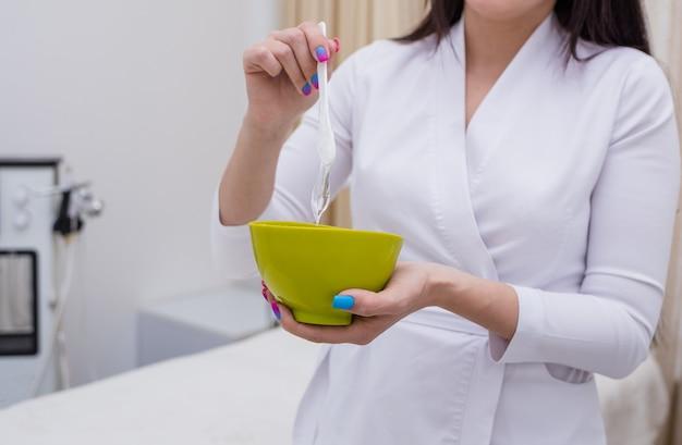 Zbliżenie kosmetologa mieszającego lekarstwo w zielonej misce