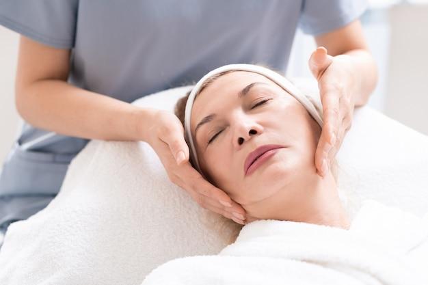 Zbliżenie: kosmetyczka masuje twarz dojrzałej klientki, relaksując się przy zabiegu