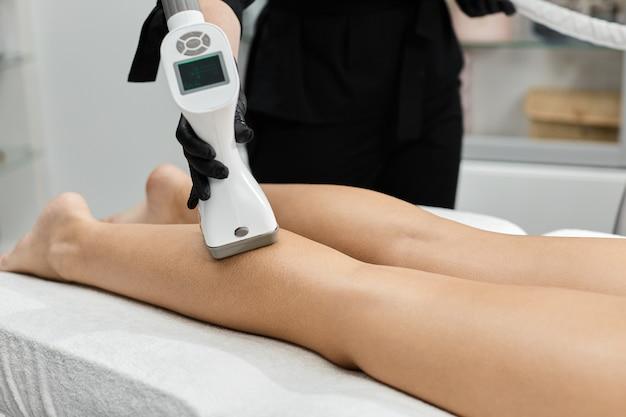 Zbliżenie: kosmetyczka ramię masowanie nogi kobiety w czarnych rękawiczkach w klinice kosmetycznej