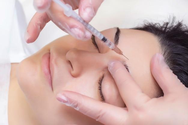Zbliżenie: kosmetyczka wstrzykuje zmarszczki na czole. ona trzyma strzykawkę. kosmetyki wstrzykuje twarz kobiety