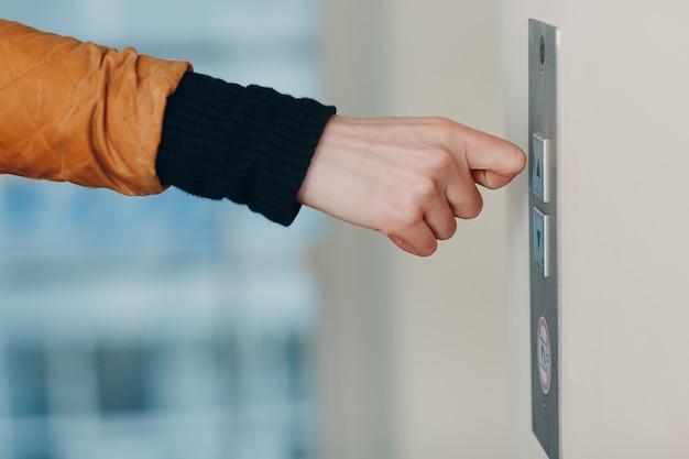 Zbliżenie kostki palca wskazującego naciskającego przycisk windy podczas pandemii koronawirusa covid-19 koncepcji kwarantanny
