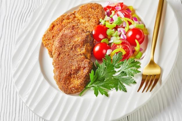 Zbliżenie kotletów jagnięcych panierowanych z pomidorem, czerwoną cebulą, sałatką z zielonego pieprzu na białym talerzu na drewnianym stole