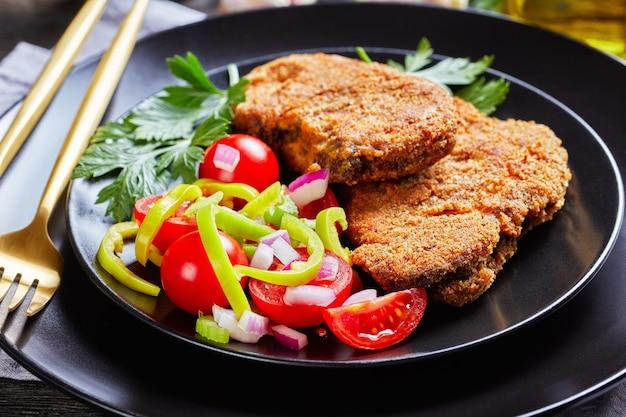 Zbliżenie kotletów jagnięcych panierowanych z pomidorem, czerwoną cebulą, sałatką z zielonego pieprzu na czarnym talerzu na drewnianym stole ze złotym widelcem i nożem, widok na krajobraz