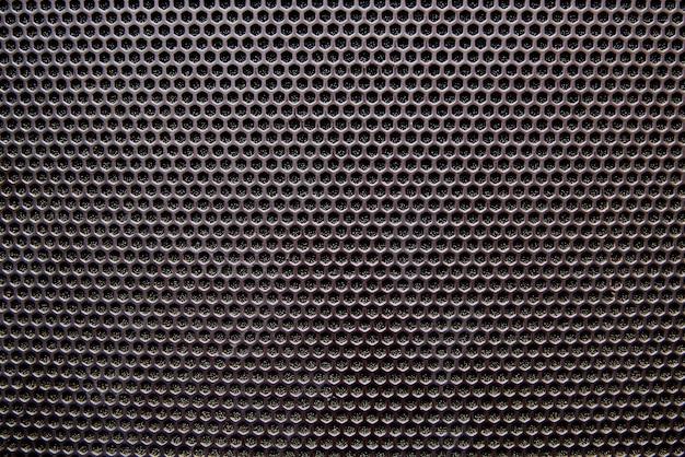 Zbliżenie kratki głośnika w czarnym tle.