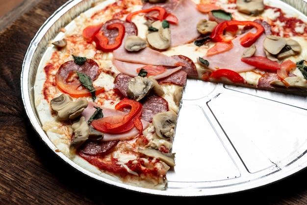 Zbliżenie krawędzi pizzy na drewnianym tle. boczek, salami, pieczarki i zielenina.