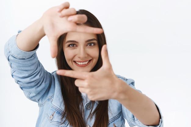 Zbliżenie kreatywna młoda fotografka szukająca inspiracji, patrząca przez sztuczny obiektyw, robiąca ramki palcami i uśmiechająca się, gdy znalazła niesamowitą scenę fotografowania, białe tło