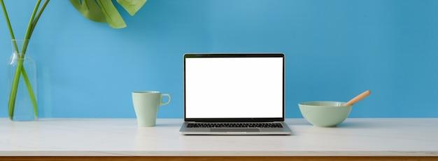 Zbliżenie kreatywnego obszaru roboczego z laptopa z pustego ekranu, posiłku i dekoracji na marmurowym biurku