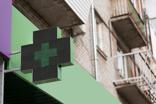 Zbliżenie krzyża medycznego na koncepcji budynku apteki, farmacji i farmakologii