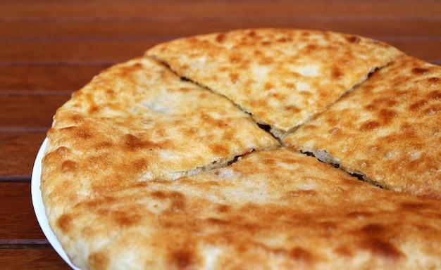 Zbliżenie kubdari, północno-zachodni gruziński tradycyjny płaski chleb nadziewany przyprawioną wołowiną lub wieprzowiną