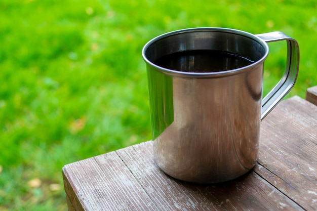 Zbliżenie: kubek podróżny na kempingu. metalowy kubek z herbatą lub kawą na drewnianym stole. skopiuj miejsce.