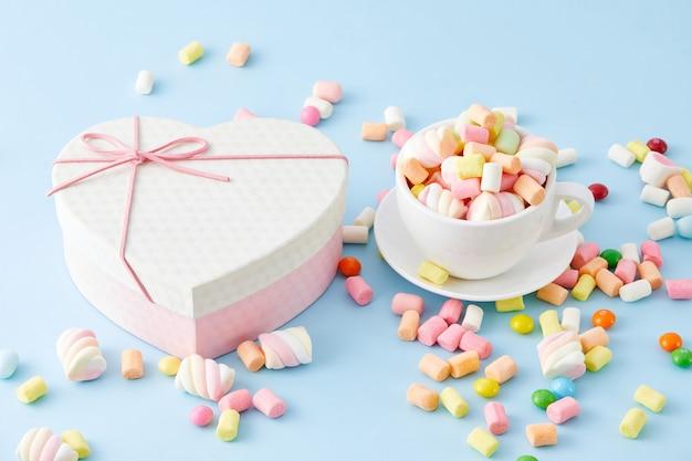 Zbliżenie kubka wypełnionego piankami marshmallow i izolowanego pudełka w kształcie serca