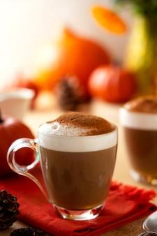Zbliżenie kubki dyni jesień latte ciepły napój z bitą śmietaną. jesienny przytulny napój.