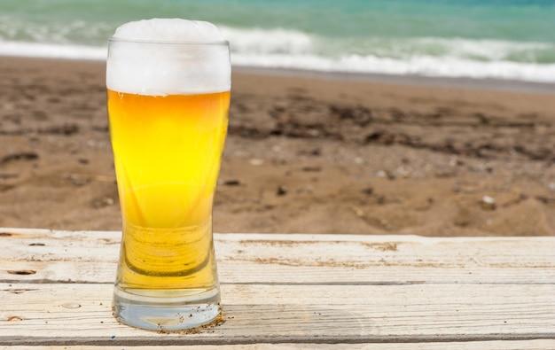 Zbliżenie kufel piwa lub piwa przy piaszczystej plaży z morzem w tle.