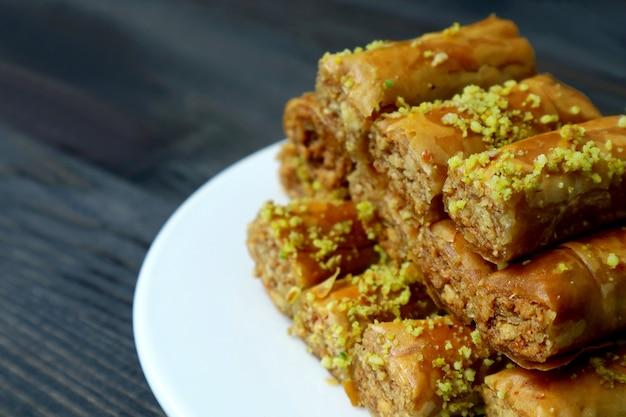Zbliżenie kupie pysznych wypieków z baklawy z orzechami pistacjowymi na białym talerzu