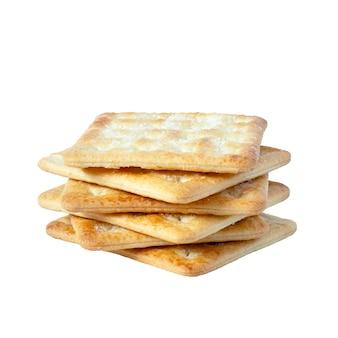 Zbliżenie kwadratowe suche krakersy na białym tle. suche ciastka suche przekąskowe zdrowe pełnoziarniste smaczne chrupiące krakersy ciasteczka dla dzieci i dorosłych, ścieżka przycinająca, widok z przodu