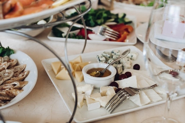 Zbliżenie: kwadratowy półmisek asortymentu świeżego sera podawanego z miodem i winogronami na weselnym stole.
